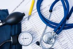 Diagnostisk utrustning - stetoskop, blodtryckmått som pre ligger på tålmodig vård- historia, och frågeformulär av tecken och royaltyfria bilder