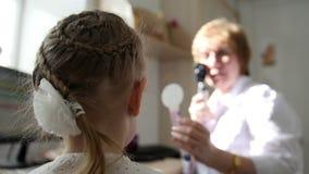 Diagnostyk w dziecka ` s okulistyce plecy głowa - optometrist diagnozy mała dziewczynka - zbiory