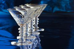 Diagon. Al row of cocktail glasses against blue background Royalty Free Stock Images