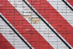 Diagonaal geschilderde bakstenenoppervlakte van muur in rode, zwart-witte kleuren, als graffiti Grafische grungetextuur van muur royalty-vrije stock afbeeldingen
