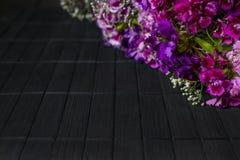 Diagonaal kader van purpere en violette bloemen op donkere houten backg royalty-vrije stock afbeeldingen