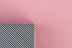 Diagonal black and white stripes on pastel pink background royalty free stock image