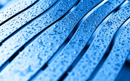 Diagonal blue bench with rain drops background. Hd Stock Photography