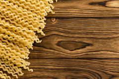 Diagonal border of dried fusili Italian pasta. Diagonal border of dried spiral or corkscrew shaped fusili Italian pasta on a wooden background with decorative stock image