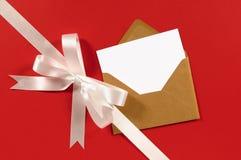 Diagonal branca da curva da fita do presente no fundo de papel vermelho com o cartão vazio da mensagem Fotos de Stock