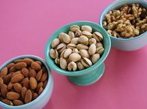 Diagonal closeup of almonds, pistachio nuts and walnuts in blue and green bowls on pink background. Three bowls of healthy, nutritious nuts for snacking or Stock Photo