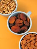 Diagonal closeup of walnut halves, dried Turkish apricots, and almonds in blue bowls on orange background. Three bowls of healthy, nutritious dried fruit and Stock Photo