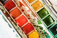 Diagonal composition and close up of a paint box showing the half pans of watercolors. In red, green, and yellow royalty free stock photography
