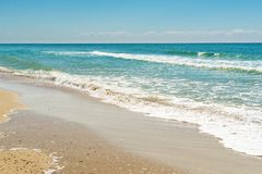 Diagonal composition of sand beach shore with the blue sea.  royalty free stock image
