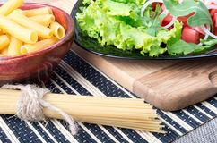Diagonal composition on a table with a fresh salad, pasta and sp. The diagonal composition on a table with a fresh salad of tomatoes, onions, lettuce and arugula royalty free stock photography