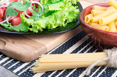 The diagonal composition on a table with a fresh salad, pasta an. The diagonal composition on a table with a fresh salad of tomatoes, onions, lettuce and arugula royalty free stock photography