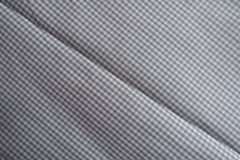Diagonal crease on chequered grey fabric Royalty Free Stock Images