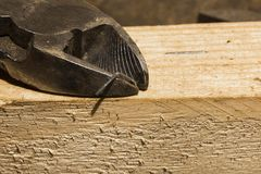 Diagonal cutting pliers cut the bracket on a wooden board royalty free stock images