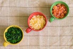Diagonal de ingredientes en tazas coloridas Foto de archivo libre de regalías
