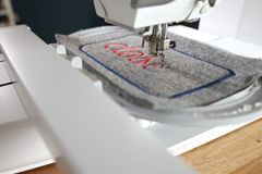 modern computerised sewing machine and embroidery unit with needle down stitching red lettering on grey felt in bright light royalty free stock photos