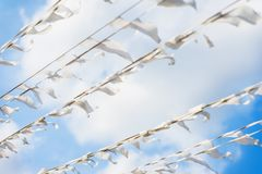 Diagonal garland of white flags of triangular shape, pennants against blue sky. City street holiday. Festival, marine. Diagonal garland of white flags of Stock Photography