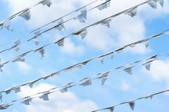 Diagonal garland of white flags of triangular shape, pennants against blue cloudy sky. City street holiday, Festival Royalty Free Stock Image