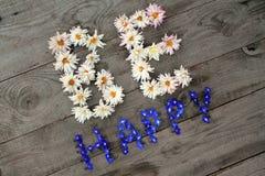 Diagonal ist Aufschrift ` glückliches ` von den Blumen auf hölzernem Hintergrund Lizenzfreies Stockfoto