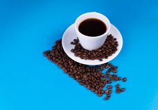 The diagonal line is made of coffee beans; a cup with a saucer is filled with coffee over the line royalty free stock photos