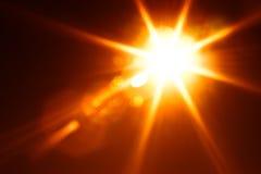 Diagonal orange glowing sun flare background Royalty Free Stock Images
