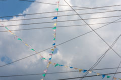 Diagonal pattern with power lines and flags against cloudy sky Stock Photo