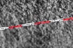 Diagonal red chain on black and white grass backdrop Stock Image