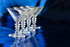Diagonal row of four cocktail glasses. Against blue background Royalty Free Stock Photography