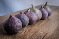 Six whole figs aligned in a row on a wooden table stock images