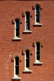 Diagonal Row of Windows. A diagonal row of tall arched windows in the side of a red brick building stock images