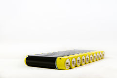 Diagonal row of yellow-black AAA alkaline batteries isolated on. Diagonal row of yellow black AAA alkaline batteries isolated on a white background with copy Royalty Free Stock Image