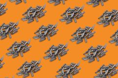 Diagonal rows of heaps of different interchangeable heads or bits for manual screwdriver for woodworking and metalworking. On orange background royalty free stock photos