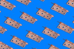 Diagonal rows of metal brown door hinges. On blue background royalty free stock image