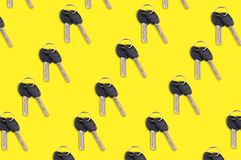 Diagonal rows of metal shiny keys with black plastic or rubber handle attached of keyring for door or car. On yellow background royalty free stock photography