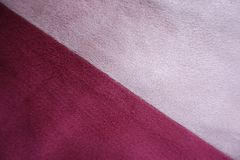 Diagonal seam between pink and red artificial suede. Fabric Stock Photos