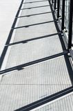 Diagonal shadows on cement walkway from metal and glass panel barrier. royalty free stock photo