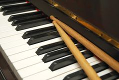 Diagonal shot of drum sticks on piano keyboard Stock Photo