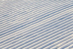 Diagonal snowcat track lines on a ski slope texture background Royalty Free Stock Image