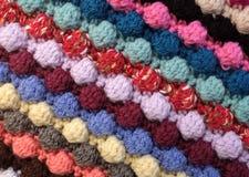 Diagonal stripes of multi-coloured bobble crochet stitches backg. Diagonal stripes of multi-coloured wool bobble crochet stitches as abstract background texture Royalty Free Stock Image