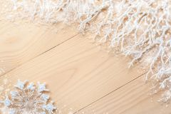 Diagonal unpainted wooden planks, white frosty branches with snow in the top right, snowflake and copy space. Stock Photo