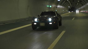 Diagonal view of blue Corvette driving through road tunnel stock video footage