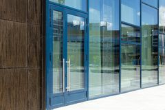 Free Diagonal View Of Modern Building Wall With Bif Glass Window And Door With Blue Frame. Street Reflection. Royalty Free Stock Photo - 162691585