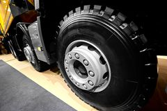 Diagonal view on tipper truck wheels and tires with blured background. Truck wheel rim. Truck chassis exhibit on car Exhibition. C royalty free stock images