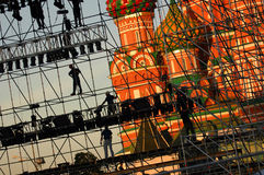 Diagonal view on workers on stage construction levels at Moscow Red Square in front of Vasiliy Blazhenniy Cathedral. Workers shado. W figures on staging Stock Photos