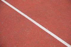 Diagonal vit linje röd stadion för markering med mjuka beläggningar för sportar Arkivfoto