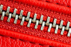 Diagonal zipper tightly closed binding together two layers of red fabric textile and red leather under high magnification detail royalty free stock image