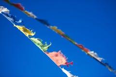 Diagonale accrochant les drapeaux bouddhistes tibétains colorés vibrants de prière Photographie stock libre de droits