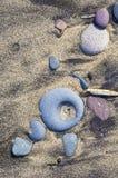 Diagonale de forme de pierres sur la plage sablonneuse Image stock
