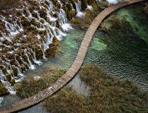 Diagonale hölzerne Brücke durch Wasserfälle Stockbilder