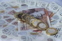 Diagonale Linie von neuen Pfundmünzen auf Kreis von zehn Pfundanmerkungen Stockbilder