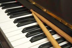 Diagonaler Schuß der Trommel haftet auf Klaviertastatur Stockfoto